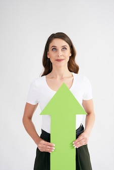 Woman looking up and holding rising arrow
