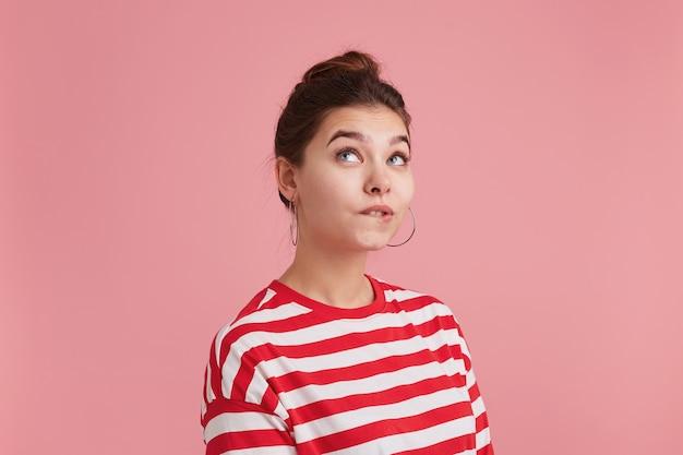 縞模様の長袖を着て左隅を見上げている女性は、感謝を感じ、成功を信じ、夢が叶うことを願っています。ピンクの背景に分離。