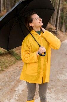 Женщина смотрит вверх, держа зонтик над головой