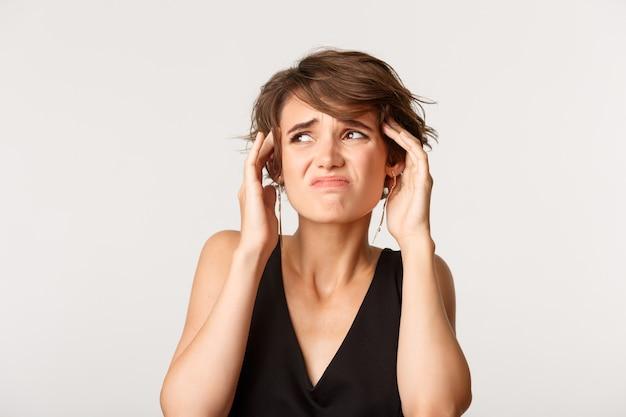 흰색 위에 서 두통에 대해 불평하는 동안 로고에서 왼쪽 상단 모서리를 찾고 여자.