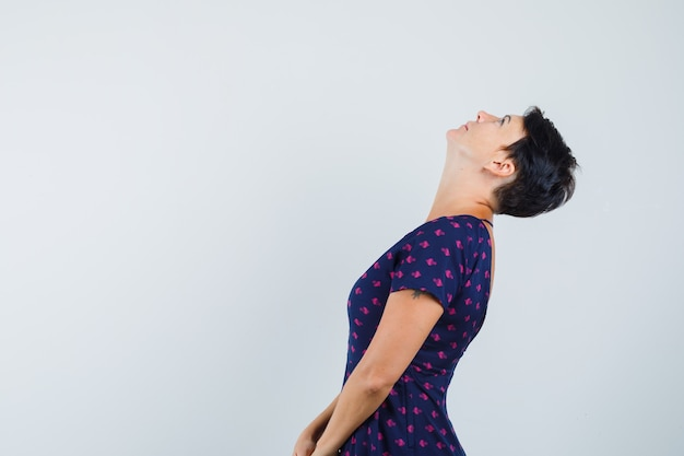 Woman looking upward while bending head back in dress and looking focused .