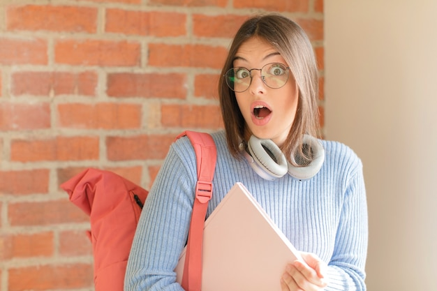 非常にショックを受けた、または驚いたように見える女性は、すごいことを言って口を開けて見つめています