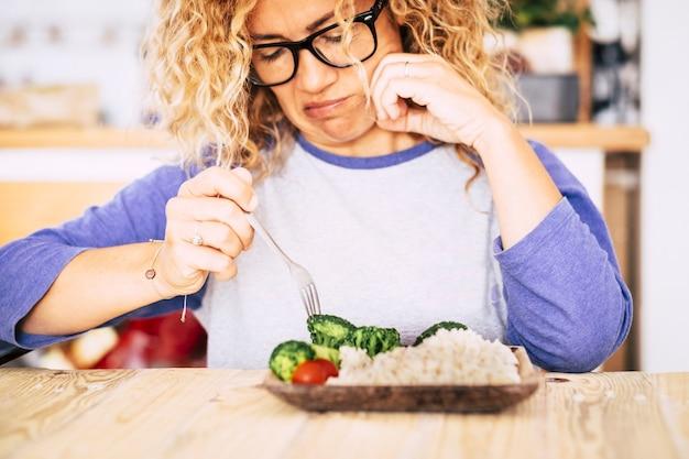 いくつかの野菜に嫌悪感を持ってテーブルの上に上がる女性-彼女は悪い栄養を好むのでこの食事をするつもりはありません-体重を減らそうとしています