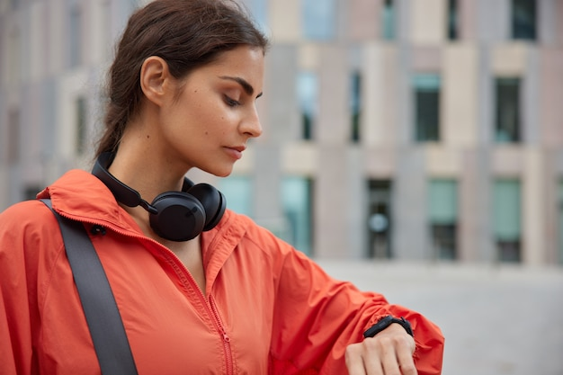 Woman looks at activity fitness tracker has workout break running application on smartwatch monitors her sport activity stands outdoor on blurred city view.
