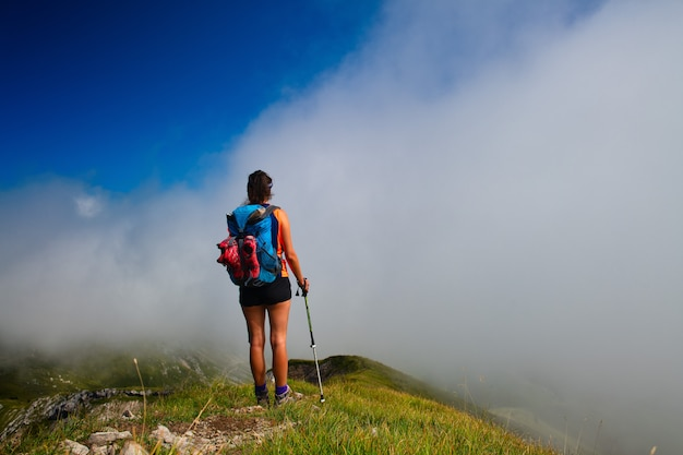 A woman looks afar in the fog at mountain valley during a walk