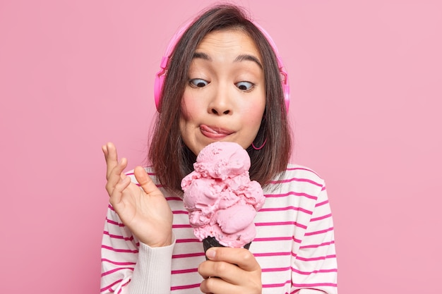 Woman looks at appetizing ice cream licks lips eats yummy frozen dessert listens music via headphones dressed in striped jumper