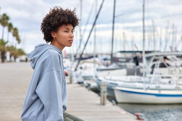 女性はマリーナハーバーでボートやヨットを見て、週末は湾の水の近くで休憩します。航海についての夢は屋外でスウェットシャツのポーズを着ています