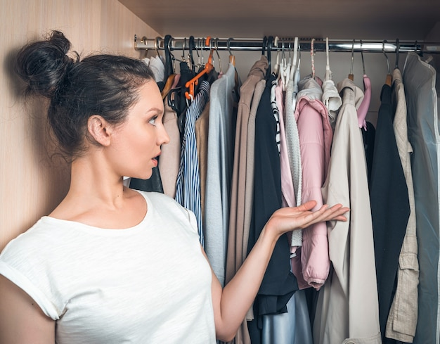 여자는 옷장에 걸려있는 물건을 놀랍고 신중하게 바라본다.