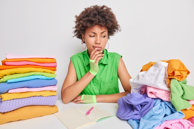 Woman looks attentively at unfolded pile of laundry busy folding clothing makes notes in notepad sits near table isolated on white