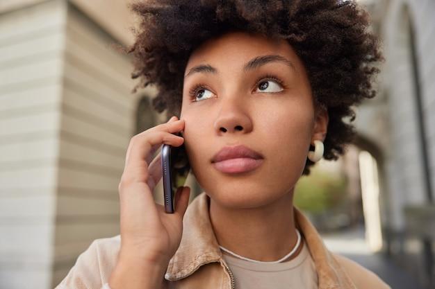 여성은 캐주얼하게 옷을 입고 국제 연결을 통해 전화를 걸고 야외에서 세포 대화를 하고 있습니다.