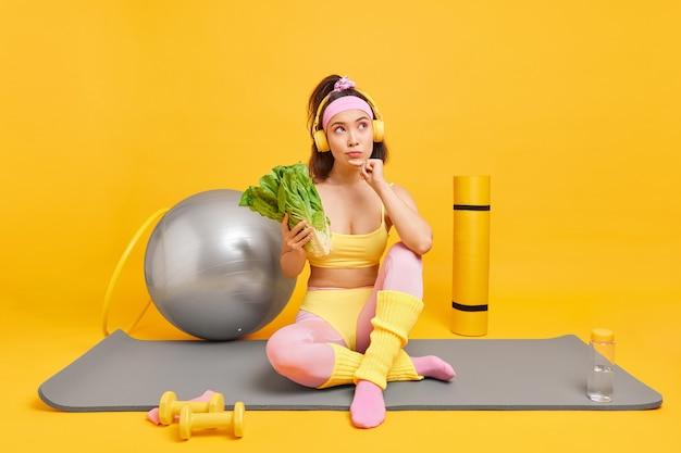 Женщина смотрит в сторону, думает, глубоко держит зеленые овощи, придерживается диеты, принимает позы для здорового питания на коврике для фитнеса, использует различное спортивное оборудование для тренировок