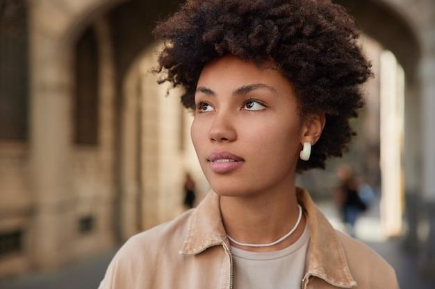 女性は思慮深くベージュのジャケットを着て目をそらしますイヤリングはどこかに見えますポーズは街を散歩します未来について考えます