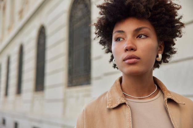 Женщина смотрит в сторону с задумчивым выражением лица, думает о чем-то, прогуливаясь по древнему городу, в стильной одежде, сосредоточенно