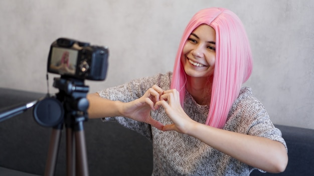 Woman looks at camera and shows heart shape sign with her palms. girl with pink hair, freelancer, blogger