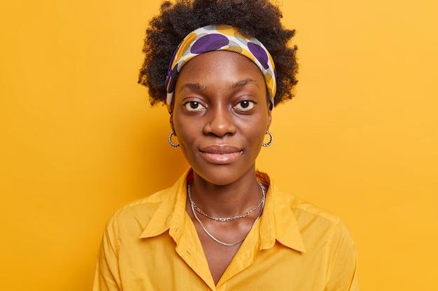 Woman looks directly at camera has big eyes full lips wears headband shirt earrings isolated on vivid yellow
