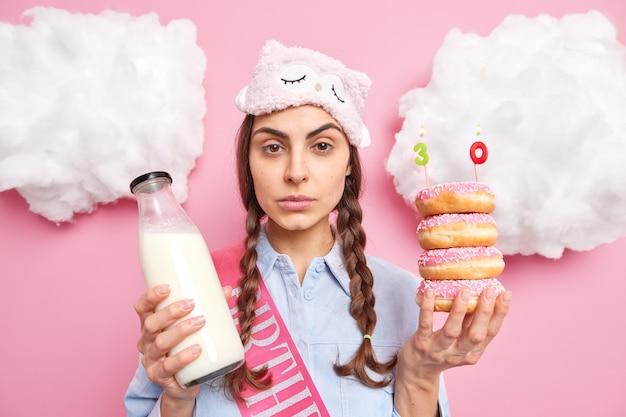 La donna guarda direttamente tiene deliziose ciambelle con le candele festeggia il 30° anniversario indossa una maschera per dormire va a fare una maschera per dormire beve latte fresco isolato sul muro rosa