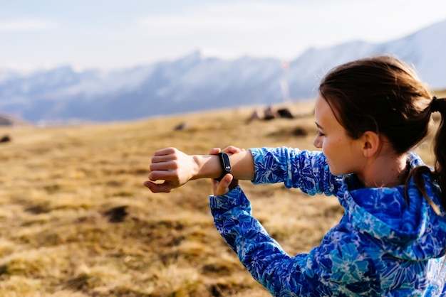 Woman looks at fitness bracelet on the background of mountains