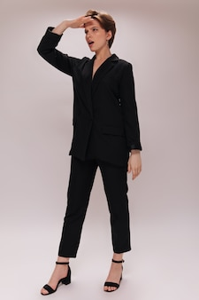 Woman looks forward. portrait of lady in black outfit on white background. short-haired girl in dark suit poses on isolated