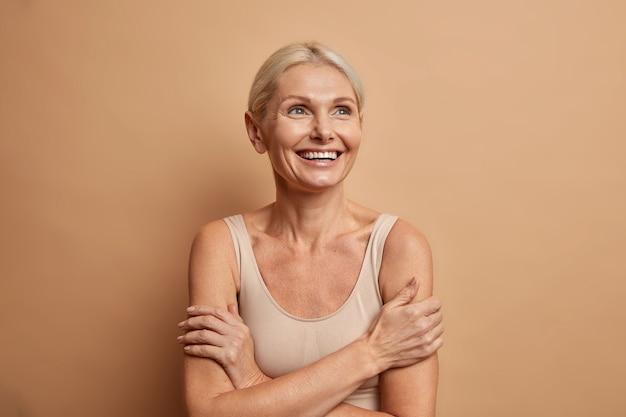 La donna guarda con gioia sopra tiene le braccia foded ha una carnagione ben curata pelle sana denti bianchi isolati su marrone