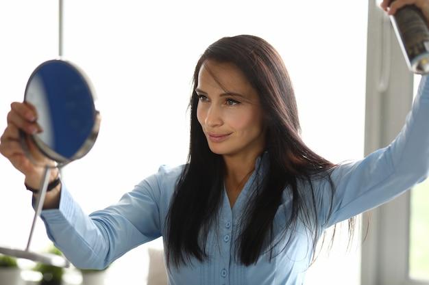 Женщина смотрит в зеркало и поправляет волосы лаком