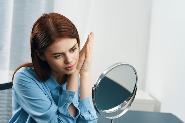 Женщина смотрит в зеркало прическа косметика утром чистая кожа. фото высокого качества