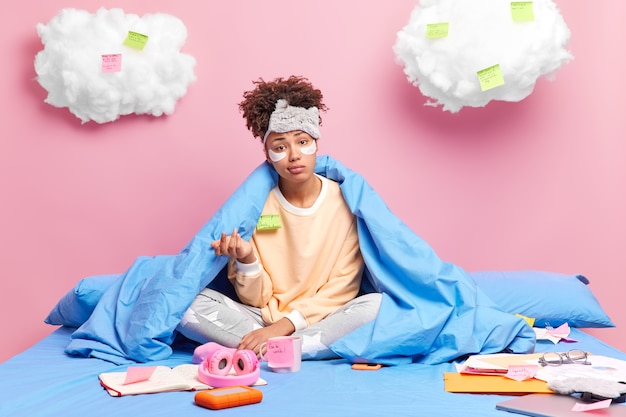 Woman looks indignant raises palm wears pajama sleepmask sits in lotus pose on comfortable bed does homework at home surrounded by diary stickers and papers