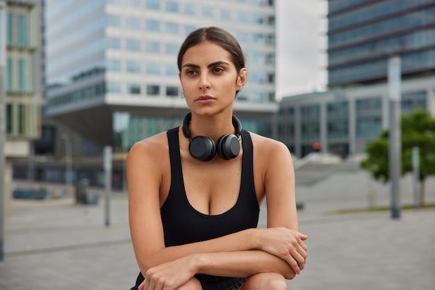 都会の環境でのトレーニングポーズがアクティブなライフスタイルをリードした後、女性は遠くを見て首の周りに黒いスポーツトップワイヤレスヘッドフォンを着用してリラックスします