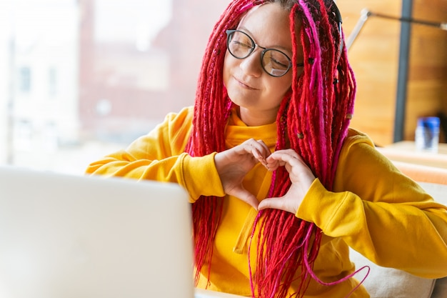 Woman looks at laptop and shows heart shape sign with her palms. live chat, stream.