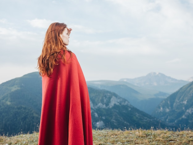 A woman looks at the mountains in nature and a red plaid on her shoulders.