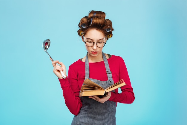 Woman looks for new recipe holding soup ladle in hands