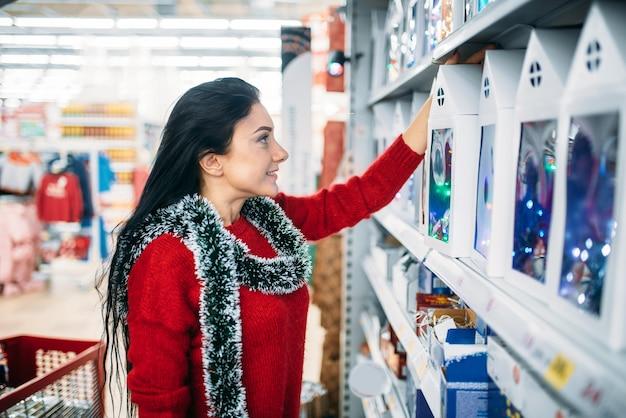 Женщина смотрит на рождественские подарки в супермаркете