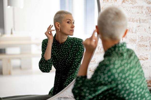 女性は鏡で自分の顔を見て、外出の準備をしています