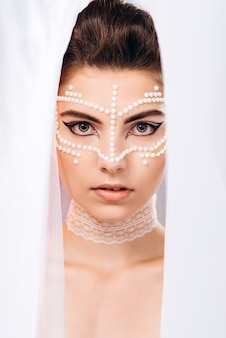 A woman looks out from under the veil and looks at the camera. fashion vertical photo