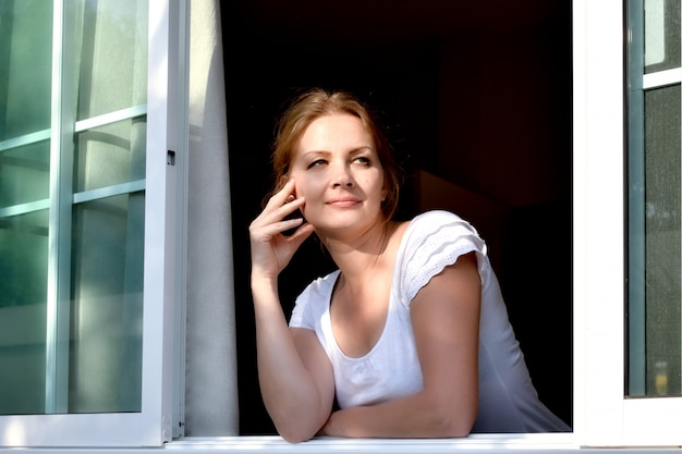 Woman looks out the window in a sunny day.