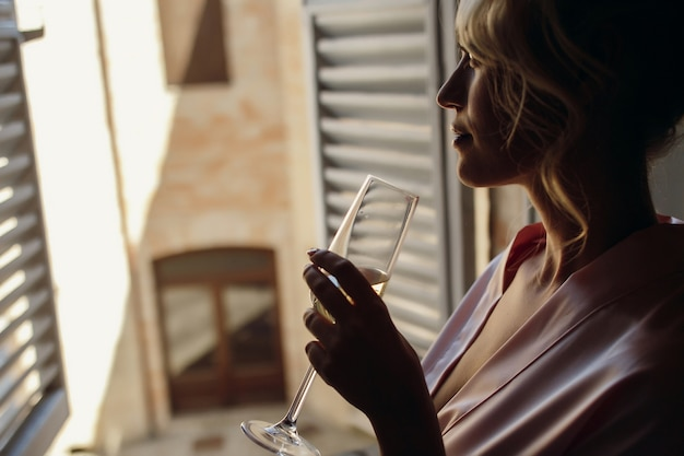 Woman looks outside standing with champagne flute