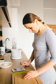 Woman looks at the recipe on the phone