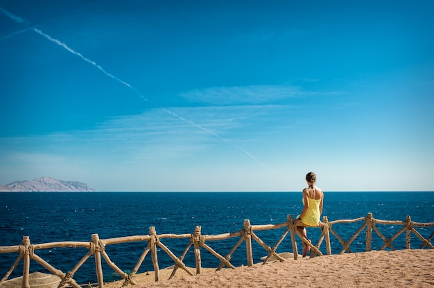 Woman looks at the sea and the island of tiran, egypt