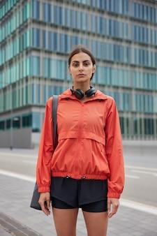 Женщина серьезно смотрит на камеру идет в тренажерный зал на тренировку несет свернутый коврик на плече, одетый в анорак и шорты, позирует на улице в большом городе