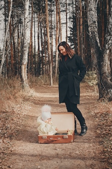 A woman looks at a small child sitting in a suitcase on the road.  change of residence, moving, accessories, fresh air, homelessness, orphanages