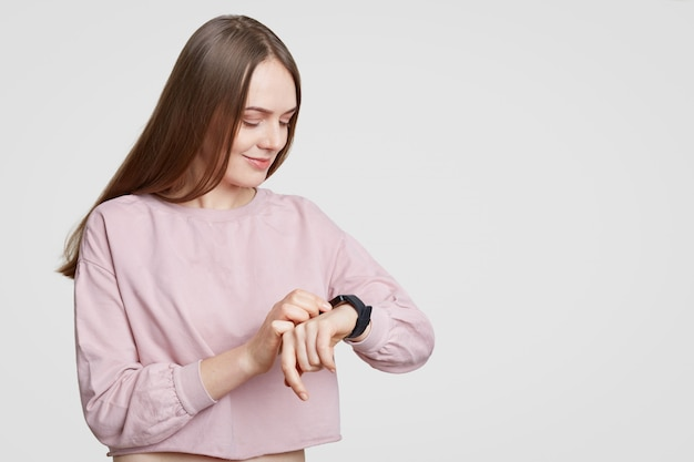 Woman looks at smartwatch, checks calories or pulse, wears casual onsized sweater, has dark staight hair, isolated on white with free space. modern technologies and innovations