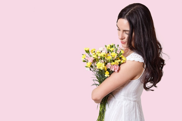 Woman looks at spring flowers, stands sideways