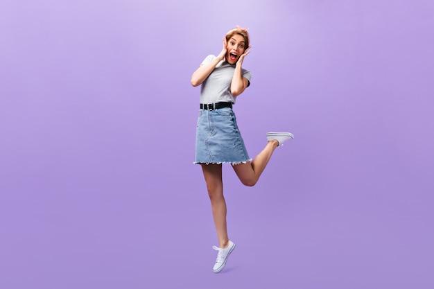 女性は紫色の背景に驚いて見えます。トレンディな衣装と白いスニーカーのポーズで素晴らしいうれしそうな女の子。n孤立した背景。