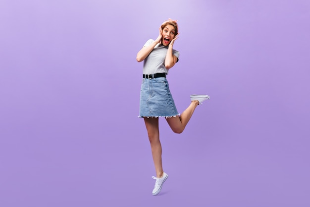 Woman looks surprised on purple background. wonderful joyful girl in trendy outfit and white sneakers posing.n isolated backdrop.