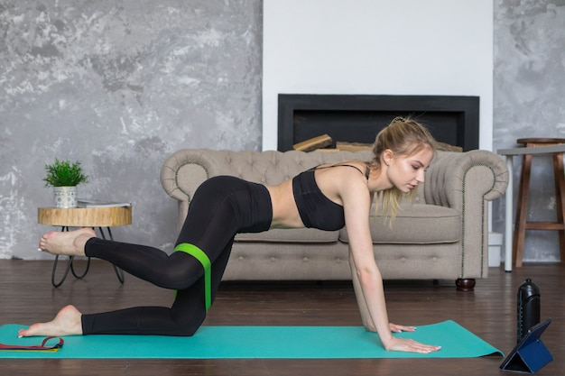 Woman looks in a tablet and sports, online workout seating at home