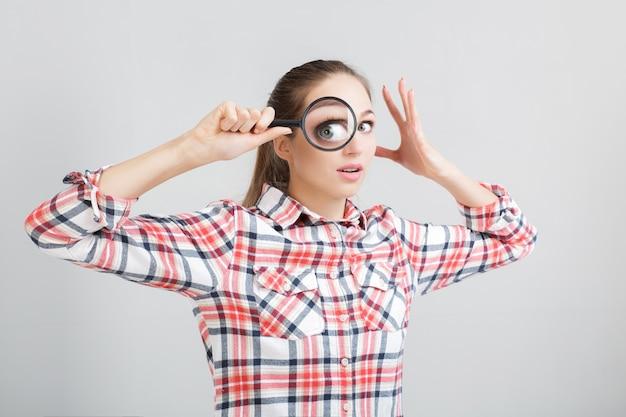 Женщина смотрит через увеличительное стекло