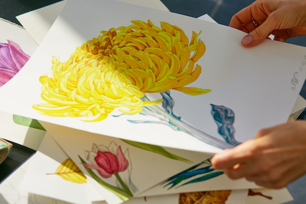 Woman looks through acrylic illustration of yellow dahlia flower