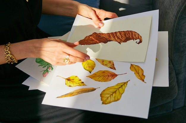Woman looks through acrylic illustrations with autumn leaves