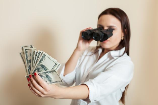 Woman looks through binoculars on money fan