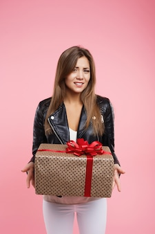 Woman looks unhappy with present box,