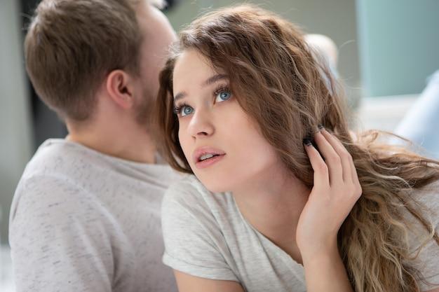 Женщина удивленно смотрит вверх, в то время как мужчина отворачивается во время спора